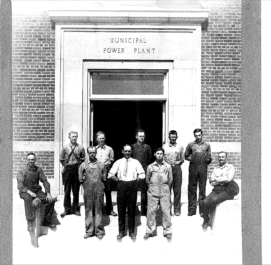 old photo of first power plant employees in front of entrance